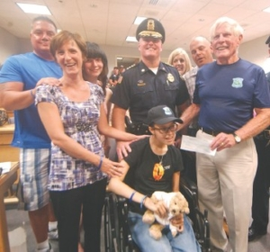 Stephanie Patenaude, seated, received a $5,000 check from the Cops For Kids with Cancer as well as the royal treatment at the Tewksbury Police Station Friday. With Patenaude are, from left, Al and Gail Daukantas, with daughter Sarah,Patenaude, who is also GailÕs daughter, Tewksbury Police Chief Timothy Sheehan and Robert Faherty, chairman of the organization. Behind them at right are Mike and Robin Patenaude. Mike is StephanieÕs father.Sun/Bob Whitaker