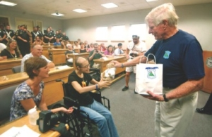 Robert P. Faherty, of Cops for Kids with Cancer, presents gifts to cancer patient Stephanie Patenaude of Tewksbury on Friday, as her mother, Gail Daukantas looks on. For video on this story, visit lowellsun.com.