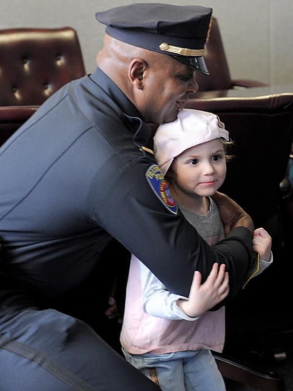 Adrianna hugs Framingham Police Lt. Lester Baker. Adrianna has acute lymphoblastic leukemia.