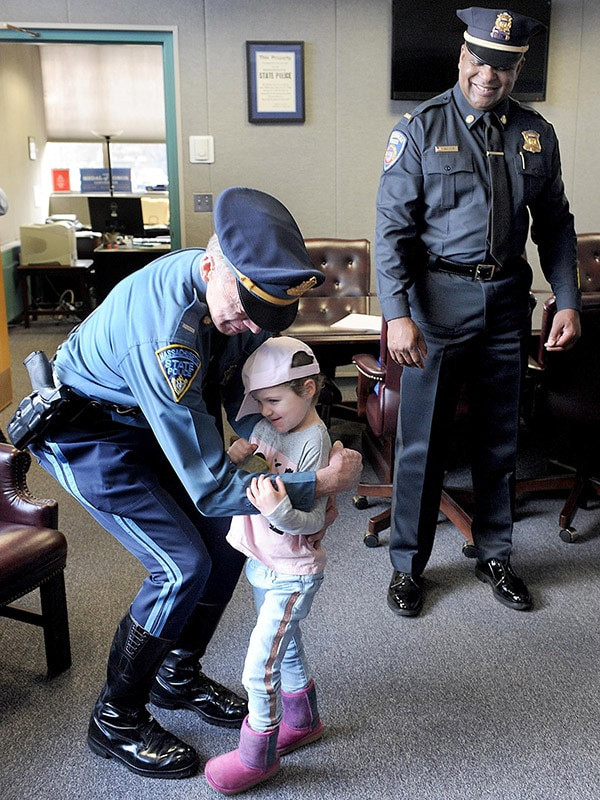 Adrianna hugs state police Lt. Bill Coulter, after hugging Lester Baker, right, at State Police headquarters.